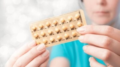 How to Use Birth Control Pills - Woman Holding Pills - Featured Image